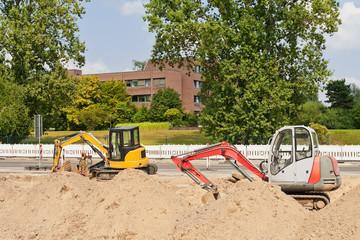 Strassenbauarbeiten - Zwei Minibagger zwischen Haufen aus Sand