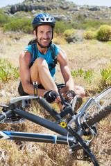 Fit cyclist tying his shoelace on mountain trail