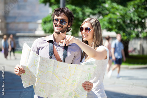 Poster Couple of tourists reading a map