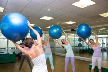 Fitness class holding up exercise balls in studio