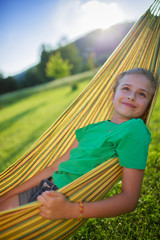 Summer joy  - lovely girl in hammock  in the garden