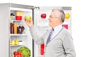 Senior man taking an apple from a refrigerator