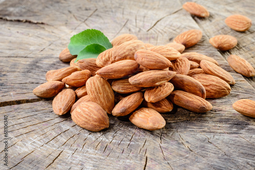 canvas print picture Almond. Nuts with leaves on wooden background