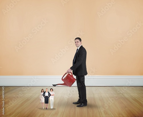 Composite image of businessman watering tiny businesswomen