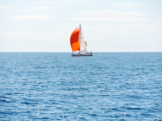 yacht with red sail in blue Adriatic sea