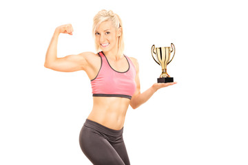 Female bodybuilder holding cup and showing bicep