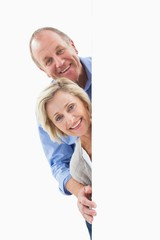Mature couple smiling behind wall
