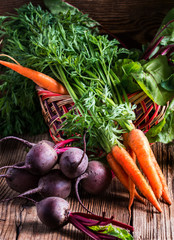 Fresh vegetables carrots, beetroots on  wooden background