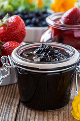 Blueberry jam strawberry jam in glass jar on wooden table