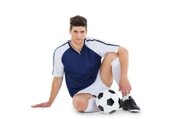 Football player sitting on the ground with ball