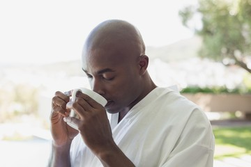 Handsome man in bathrobe drinking coffee outside