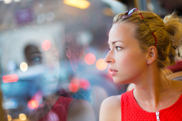 Woman looking out tram's window.