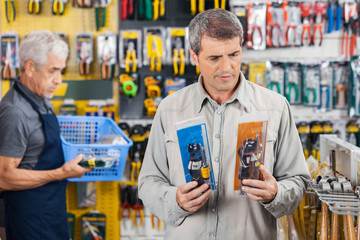 Customer Choosing Soldering Iron At Hardware Store