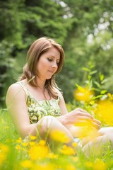 Thoughtful woman relaxing in field