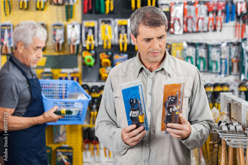 Customer Choosing Soldering Iron At Hardware Store - 68107753