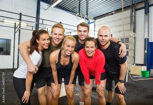 Tuinposter Gymnastiek Group Of Happy Athletes Standing At cross fitness box