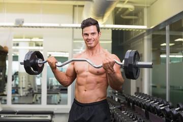 Smiling shirtless muscular man lifting barbell in gym
