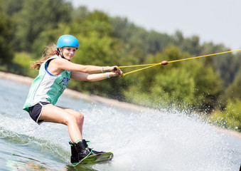 Blonde Frau mit Helm beim Wakeboarden