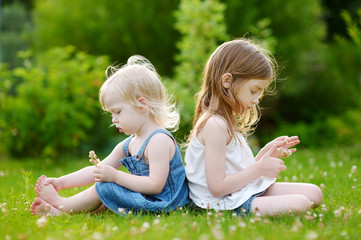 Two cute little sisters sitting on the grass