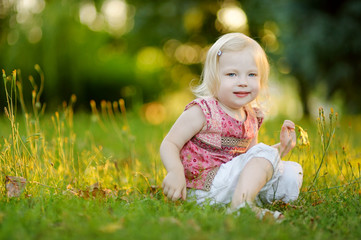 Cute little toddler girl sitting on the grass
