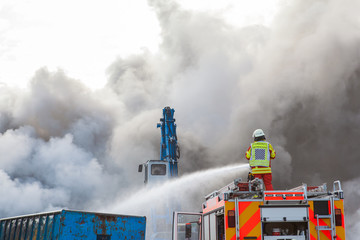 Fireman fighting a fire from the top of the truck