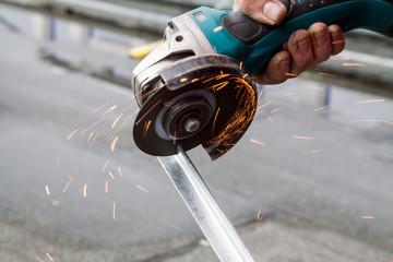 Man cutting a metal bar with a circular saw