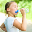 Cute girl drinks water from a plastic bottle