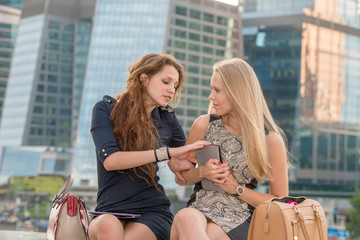 Two beautiful girl with tablet pc communicate near skyscrapers.