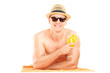 Shirtless guy lying on towel and drinking a cocktail