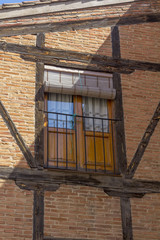 window in old house with wooden beams and bricks