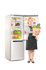 Woman with bag of groceries in front of a fridge