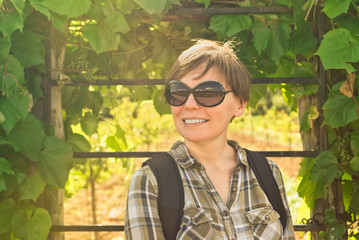 Smiling young adult woman in vineyard