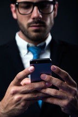 Handsome stylish man in elegant black suit using mobile phone.