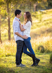 young couple standing in embrace in a rural setting
