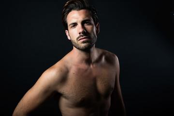 Handsome muscular male model posing over black background.
