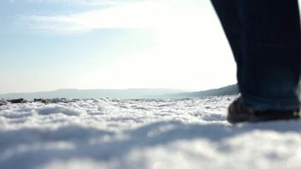 Ein Pärchen spaziert händchenhaltend am Winterstrand