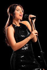 Female musician singing on a microphone