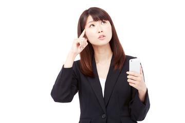 スマートフォンを持って考えるビジネスウーマン