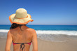 canvas print picture - Woman in hat overlooking the seascape from the beach