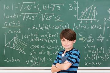 intelligenter junge vor einer tafel mit formeln