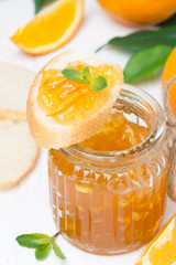 orange jam in a glass jar and fresh baguette