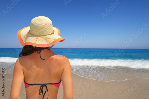 canvas print picture Woman in hat overlooking the seascape from the beach