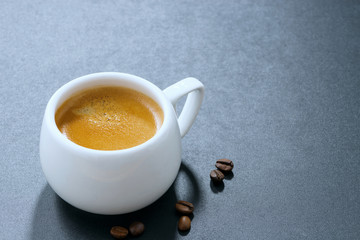 white cup of espresso and coffee beans on a dark background
