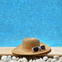 Straw hat and white glasses by the poolside