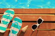 Flip flops and sunglasses on wooden planks and water - 68115313