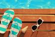 Leinwandbild Motiv Flip flops and sunglasses on wooden planks and water