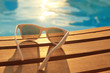Sunglasses on wooden planks and water on sunset - 68115317
