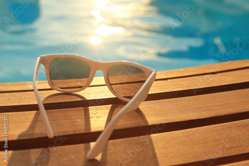 Leinwandbild Motiv Sunglasses on wooden planks and water on sunset
