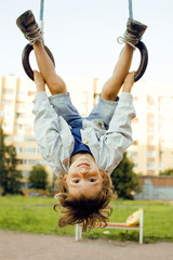 little cute boy hanging on gymnastic ring