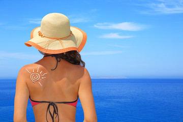 Sun made of sunblock on woman back with seascape background